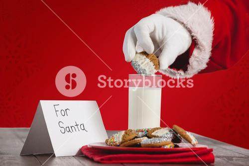 Composite image of cropped image of santa claus dipping cookies in glass of milk