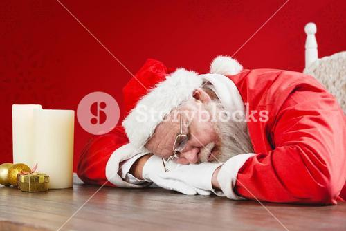 Composite image of santa claus sleeping at desk