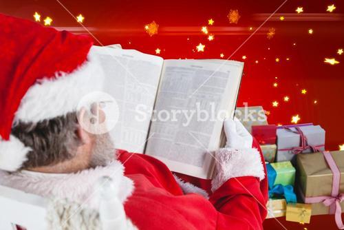 Composite image of santa claus reading bible with christmas present beside him