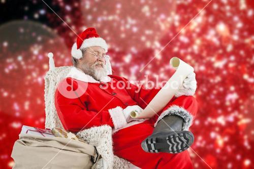 Composite image of santa claus smiling and reading christmas wish list