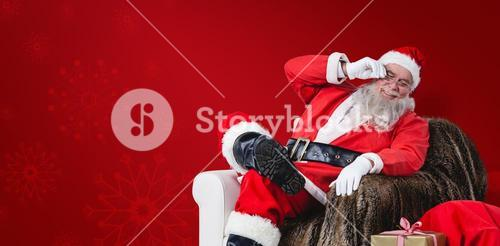 Composite image of santa claus sitting on sofa with sack of christmas present beside him