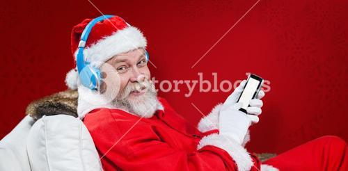 Composite image of santa claus with headphones using mobile phone