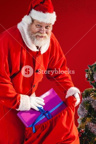 Composite image of santa claus putting christmas presents in christmas bag