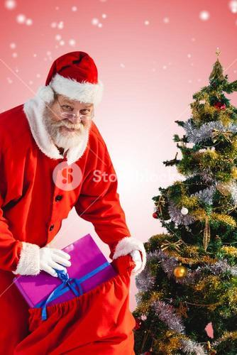 Composite image of santa claus putting presents in bag by christmas tree
