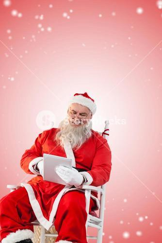 Composite image of santa claus playing game on digital pc