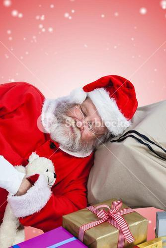 Composite image of high angle view of santa claus sleeping beside christmas presents