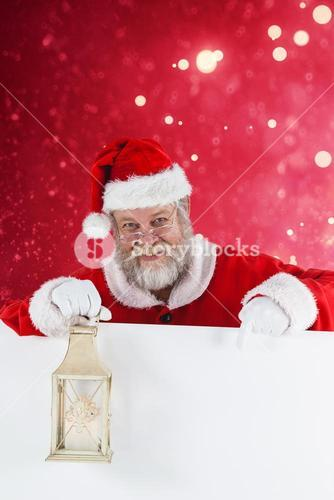 Composite image of santa claus holding christmas lantern