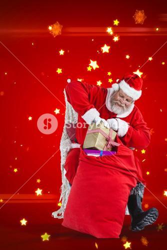 Composite image of santa claus putting presents in christmas bag