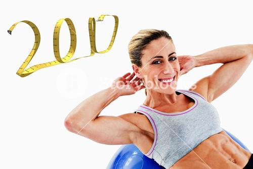3D Composite image of fit woman doing sit ups on blue exercise ball smiling at camera