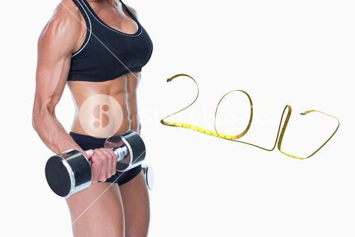 3D Composite image of female bodybuilder working out with large dumbbells mid section