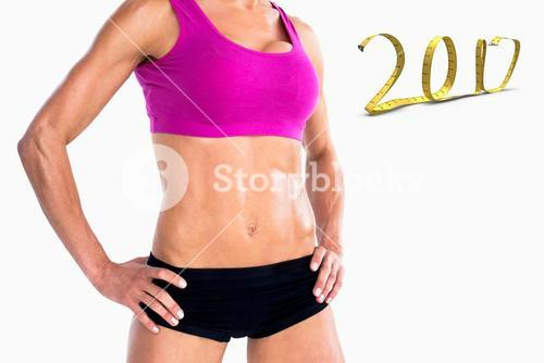 3D Composite image of female bodybuilder posing with hands on hips mid section
