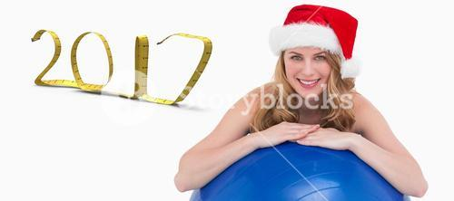 3D Composite image of festive fit blonde leaning on exercise ball