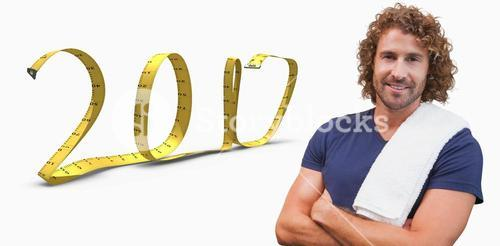 3D Composite image of smiling handsome trainer with arms crossed in gym