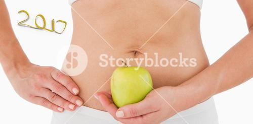 3D Composite image of fit woman holding an apple in front of her belly