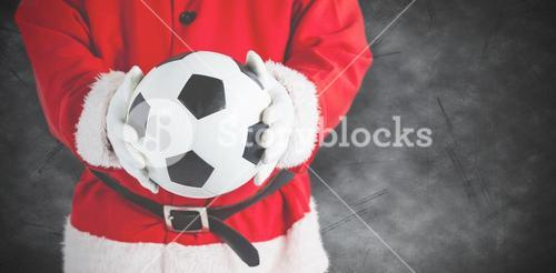 Composite image of santa claus holding a football