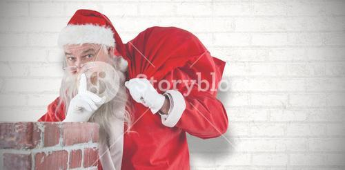 Composite image of santa claus with finger on lips standing beside chimney
