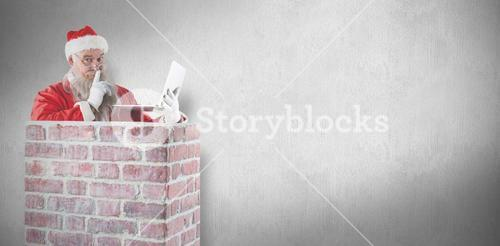 Composite image of santa claus using laptop by chimney