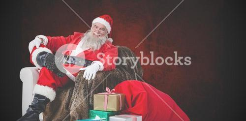 Composite image of portrait of santa sitting on sofa with sack of christmas present beside him