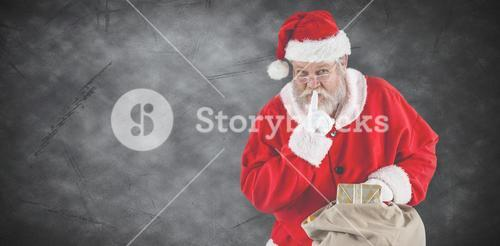 Composite image of santa claus with finger on lips and holding a gifts