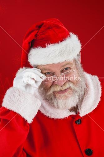 Composite image of santa claus looking through spectacles