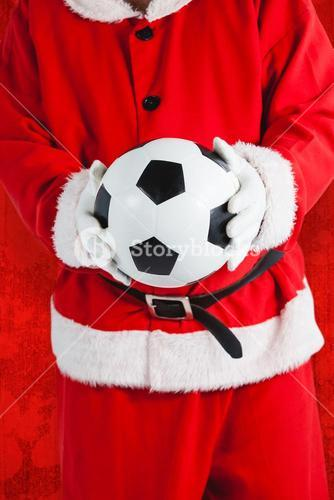 Composite image of santa claus holding football