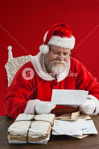 Composite image of santa claus reading wish lists
