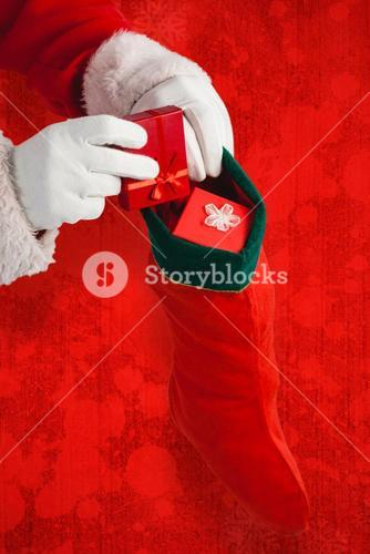 Composite image of santa claus putting presents in christmas stockings