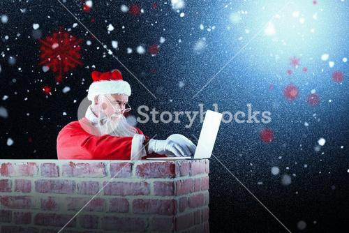 Composite image of santa claus using laptop on chimney