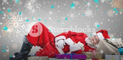 Composite image of santa claus resting beside christmas gifts