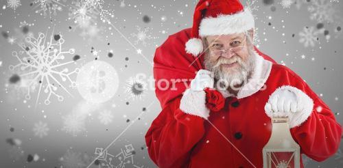 Composite image of santa claus holding christmas bag and lantern