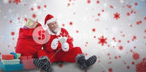 Composite image of santa claus sitting by christmas gifts counting bills