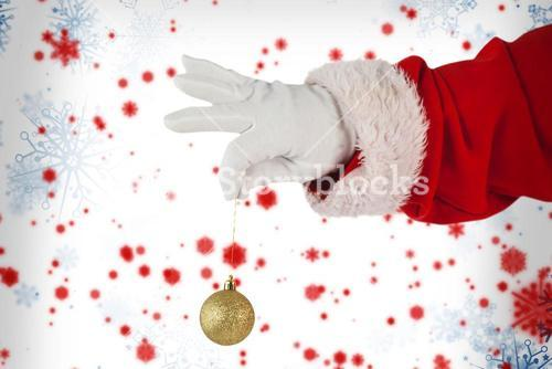 Composite image of santa claus holding christmas bauble