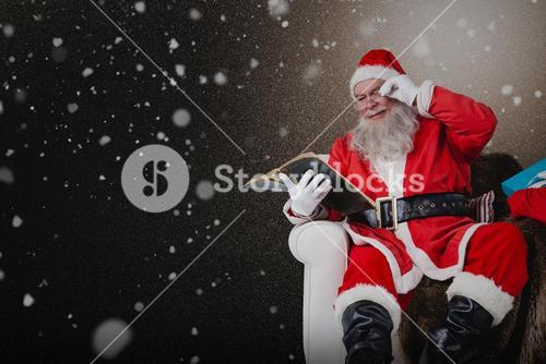 Composite image of santa reading bible with sack of christmas present beside him