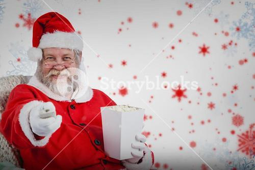 Composite image of santa claus having popcorn while watching tv