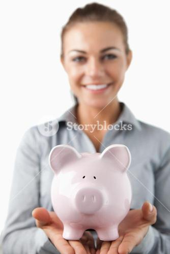 Close up of piggy bank being held by smiling female bank assistant