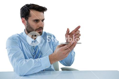 Businessman pretending to touch an invisible object at desk