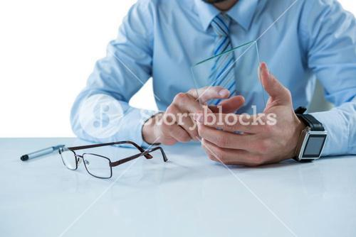 Businessman sitting at table touching a glass sheet