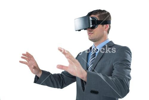 Businessman using virtual reality headset against white background