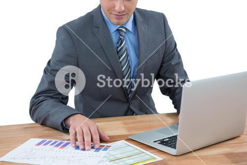 Businessman using laptop while checking graph in office