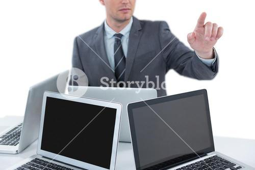 Businessman gesturing while sitting at table with four laptops