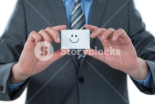 Businessman holding visitor card with smiley