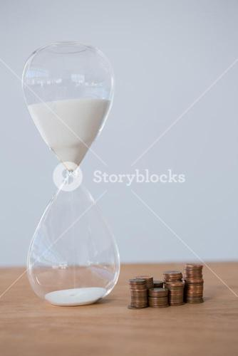 Hourglass and stacks of coins on table