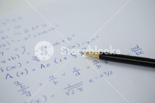 Pen over a sheet of paper with maths formulas