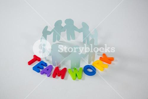 Circle of paper cut-out figures with teamwork word