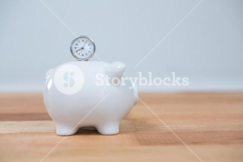 Close-up of piggy bank and clock