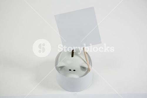 Close-up of piggy bank with placard sign board