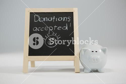 Donation accepted written on slate with piggy bank