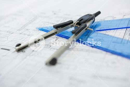 Blueprint with ruler and thumbscrew compasses
