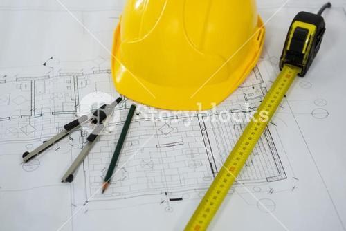 Blueprint with tape measure, pencil , thumbscrew compasses and hard hat