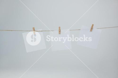 Three sticky notes hanging on clothes line